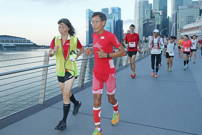 Ultramarathoner (second from left) Lim Nghee Huat, with his wife (left) Deborah Mok, together with support runners, covering 10 loops around Marina Bay on their last leg of running 50km every day for 50 days.-- ST PHOTO: SEAH KWANG PENG