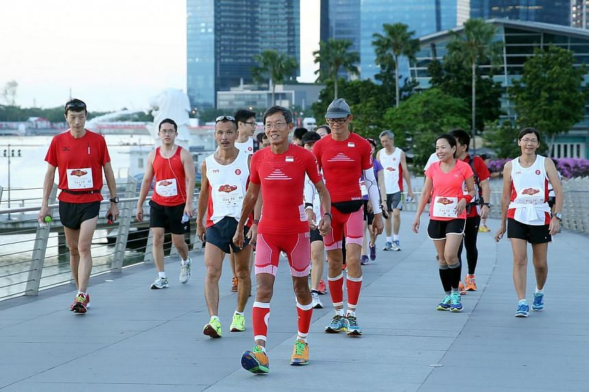 Ultramarathoners (centre, in red) Lim Nghee Huat and (centre, right, in red) Yong Yuen Cheng, and their support runners, cover ing10 loops around Marina Bay on their last leg of running 50km every day for 50 days.-- ST PHOTO: SEAH KWANG PENG