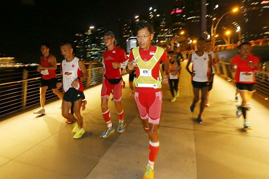 Ultramarathoners (centre) Lim Nghee Huat and (centre, left) Yong Yuen Cheng and their support runners, covering 10 loops around Marina Bay on their last leg of running 50km every day for 50 days. -- ST PHOTO: SEAH KWANG PENG