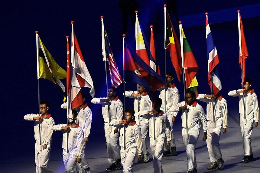Flag bearers from the 11 Asean countries march during the opening ceremony of the 28th SEA Games at the National Stadium on June 5, 2015. -- PHOTO: AFP