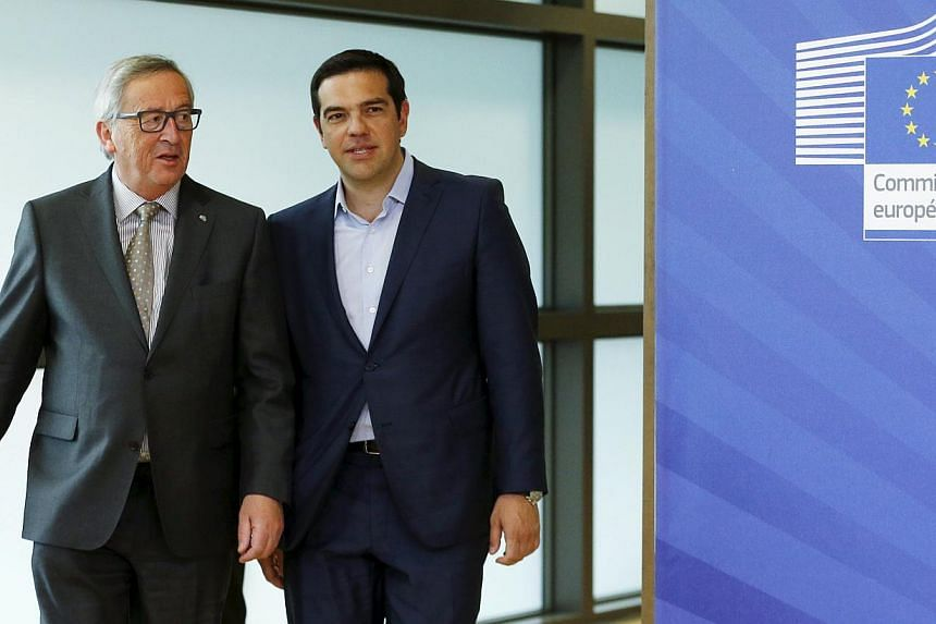 Greece's Prime Minister Alexis Tsipras (right) walking with European Commission President Jean-Claude Juncker (left) ahead of a meeting at the EU Commission headquarters in Brussels, Belgium, on June 3, 2015. -- PHOTO: REUTERS