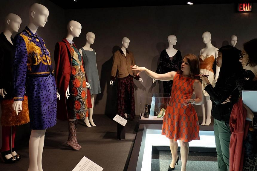 People looking at a display during the press preview for the Global Fashion Capitals exhibition at the Fashion Institute of Technology in New York on June 2, 2015. -- PHOTO: AFP