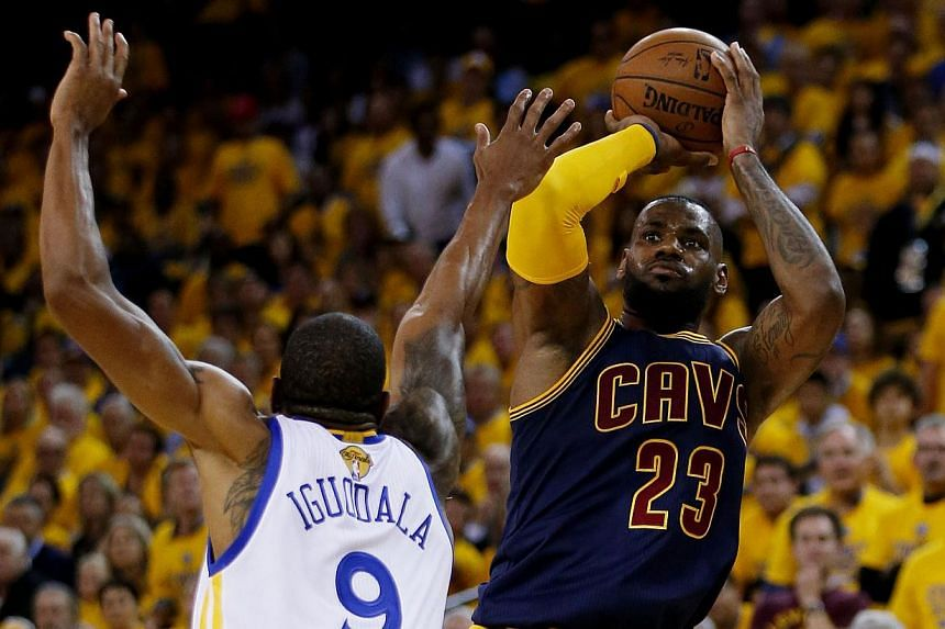 LeBron James of the Cleveland Cavaliers shooting against Andre Iguodala #9 of the Golden State Warriors in the fourth quarter during Game One of the 2015 NBA Finals on June 4, 2015, in Oakland, California. -- PHOTO: AFP