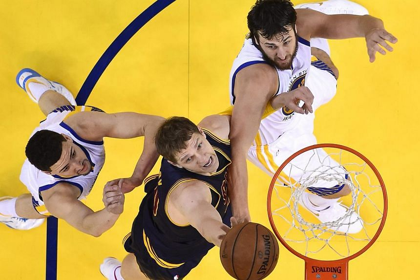 Cleveland Cavaliers player Timofey Mozgov (centre) going for a rebound against Golden State Warriors players Andrew Bogut (right) and Klay Thompson (left) in the first half of Game One of the NBA Finals in Oakland, California, on June 4, 2015. -- PHO