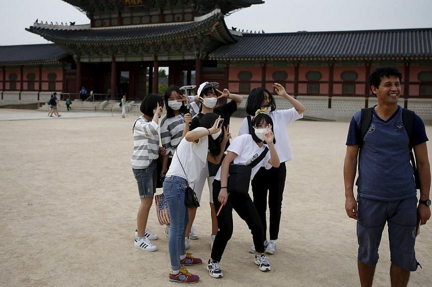 South Korean students wearing masks to protect against the Middle East Respiratory Syndrome (Mers) standing behind a tourist as he poses for photographs at the Gyeongbok Palace in central Seoul on June 4, 2015. -- PHOTO: REUTERS