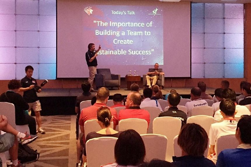 """Singapore's national swim coach Sergio Lopez (standing) with guest speaker and three-time head coach of the US Olympics men's swimming team Eddie Reese (seated) on stage during the inaugural """"Swim with Us by Sergio Lopez"""" coaching clinic at the Pan P"""