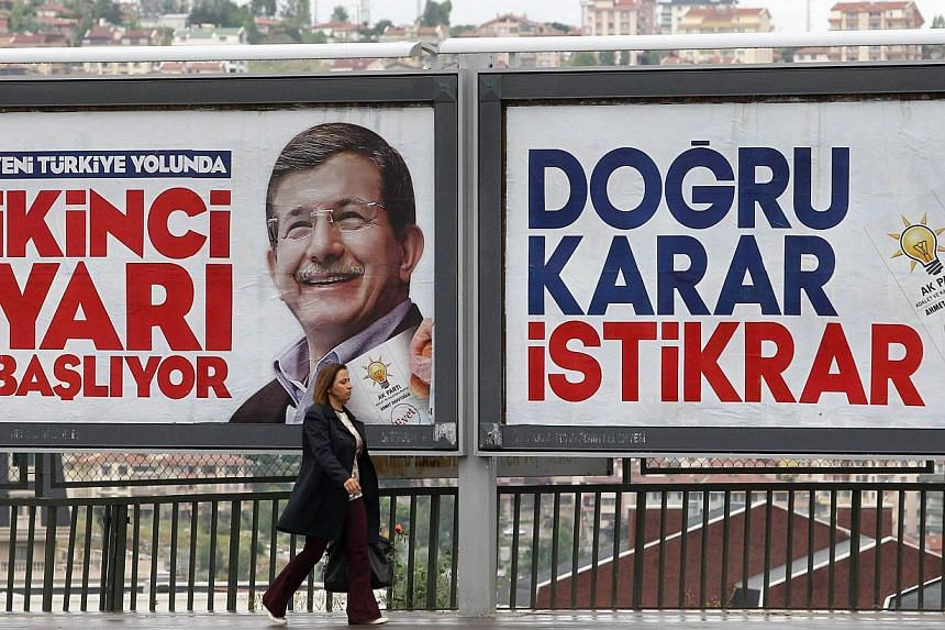 A woman walking in front of a campaign poster of Turkish Prime Minister Ahmet Davutoglu in Ankara Turkey, on June 4, 2015. -- PHOTO: AFP