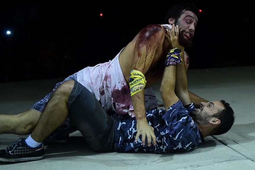 A man wearing cinema style make-up to resemble a zombie (left) wrestling with anther during the role game Survival Zombie in Olias del Rey on May 30, 2015.-- PHOTO: AFP