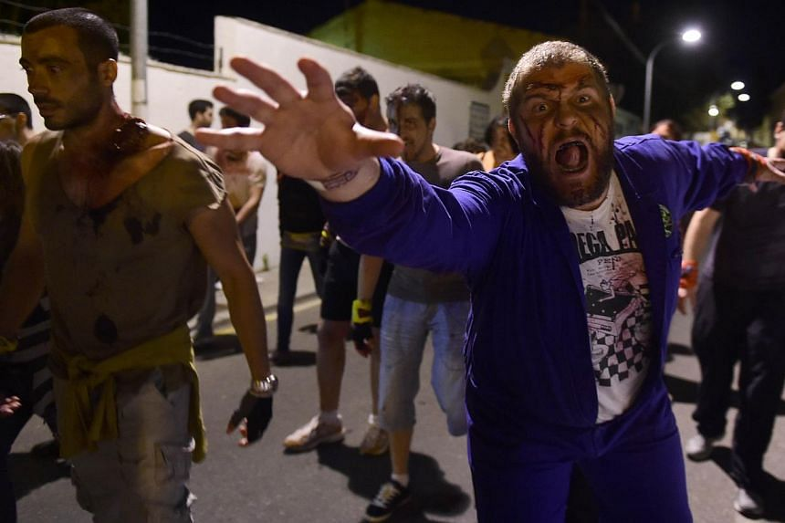 People wearing cinema style make-up to resemble zombies walking along a street during the role game Survival Zombie in Olias del Rey on May 30, 2015. -- PHOTO: AFP