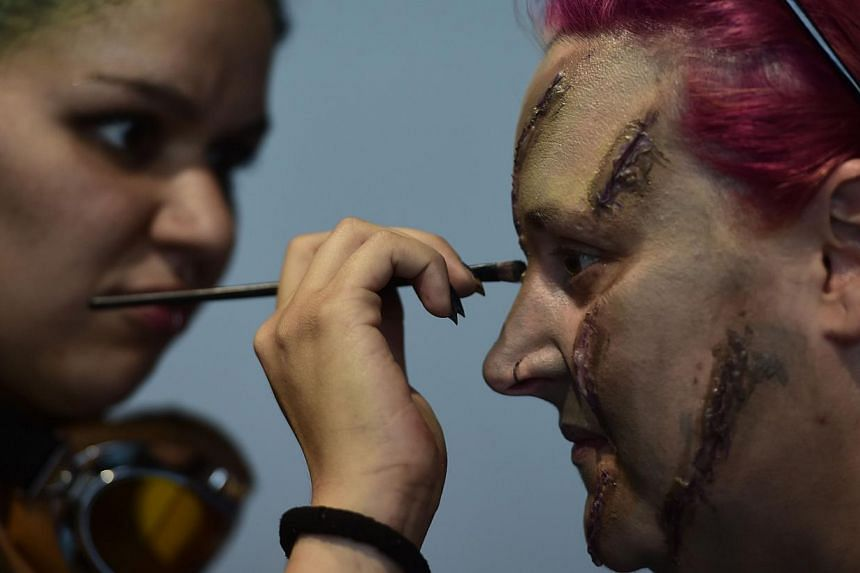 A woman (left) applying make-up to the face of a participant for