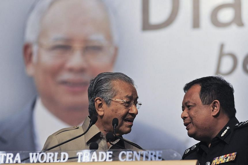 A police officer stepping on stage to ask former Malaysian prime minister Mahathir Mohamad to stop speaking during the Nothing2Hide forum in Kuala Lumpur on June 5, 2015. -- PHOTO: EPA