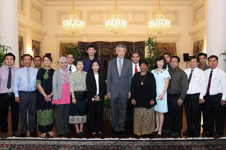 Prime Minister Lee Hsien Loong posing for a photo with 17 visiting journalists from the nine other Asean countries. Mr Lee hosted an interview with the group at the Istana on June 4, 2015. -- PHOTO: MCI