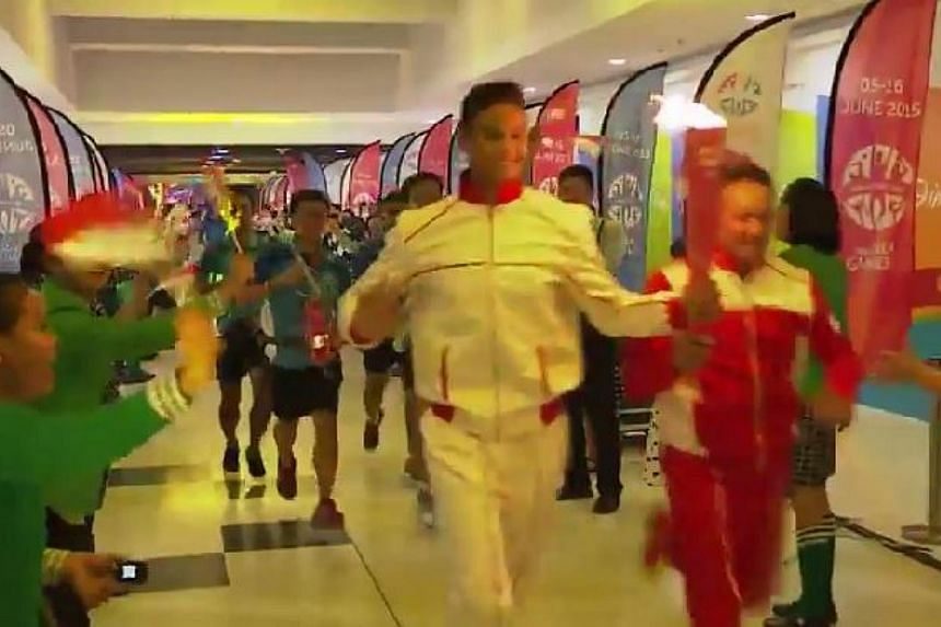 Fandi Ahmad and his son Irfan with the SEA Games torch. -- PHOTO: SPORT SINGAPORE/YOUTUBE