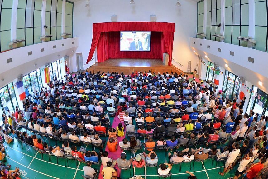 People at Bishan Community Club watching a World Cup football match in 2014. Selected CCs will be showing SEA Games events, including the opening ceremony on Friday evening, and live screenings of sports events, the People's Association said. -- PHOT