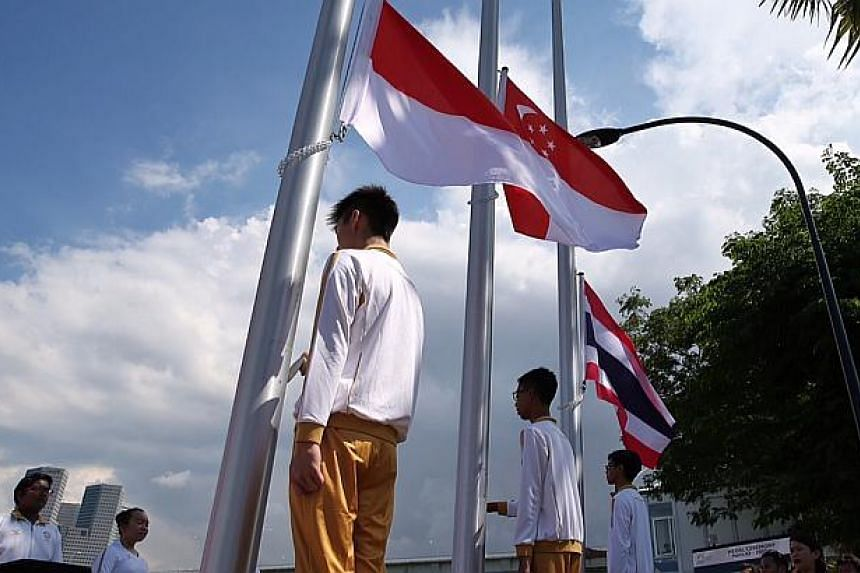 The Singapore flag being raised at the Marina Channel during the victory ceremony for the SEA Games' canoeing men's K2-1000m final. -- ST PHOTO: NEO XIAOBIN