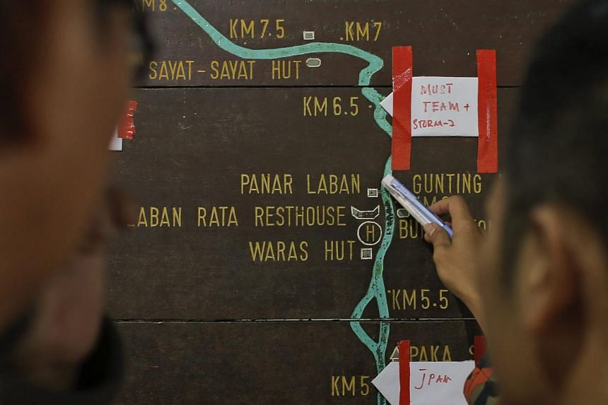 Malaysian rescue officials marking locations on an information board on the way to Mount Kinabalu during the rescue mission for more than 130 climbers stranded on one of South-east Asia's highest peaks after an earthquake rocked parts of Sabah, on Ju