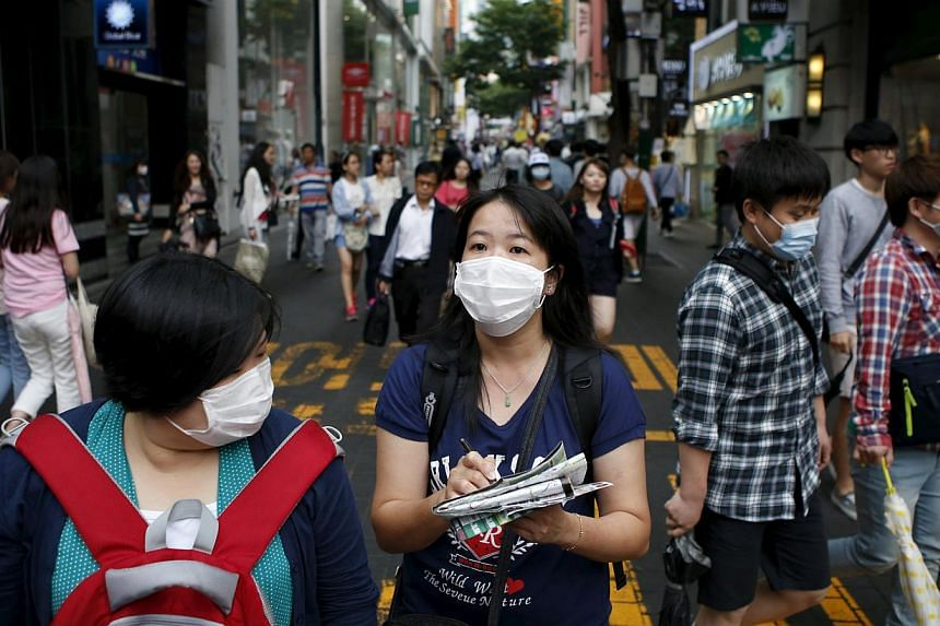 Tourist wearing masks walking at Myeongdong shopping district in central Seoul, South Korea, on June 5, 2015. -- PHOTO: REUTERS