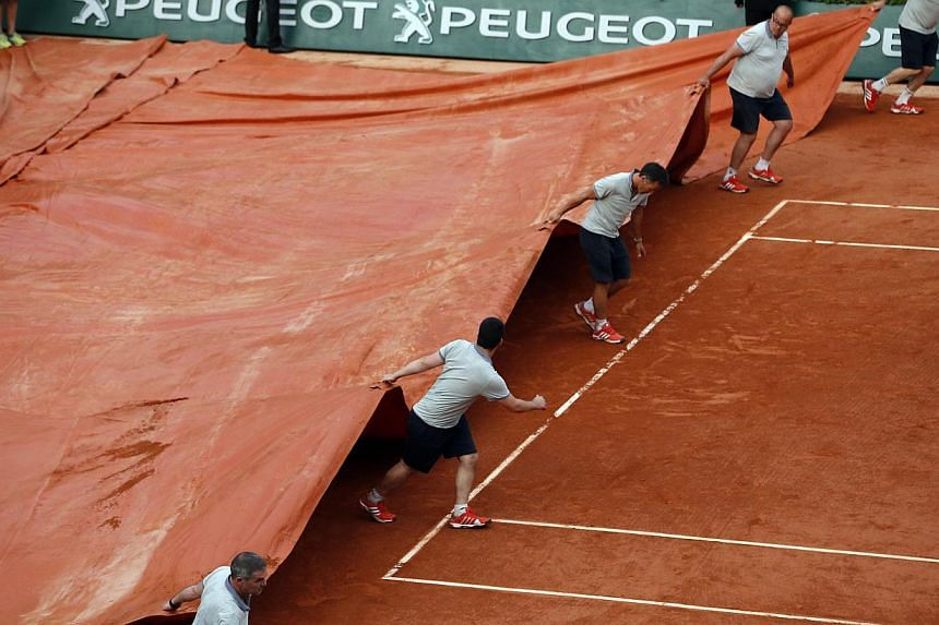 Ground staff covering the tennis court after the match between Novak Djokovic of Serbia and Andy Murray of Britain was called off due to a severe storm, on Friday, June 5, 2015. -- PHOTO: EPA