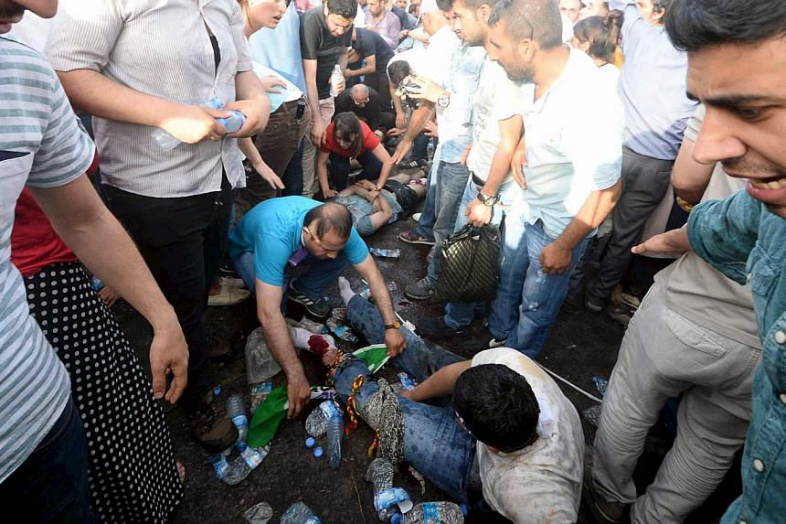 Injured people get first aid after an explosion during an election rally of the pro-Kurdish Peoples' Democratic Party (HDP) in Diyarbakir, Turkey, on June 5, 2015. Two people were killed and over 100 were injured when two explosions hit the rally, ju