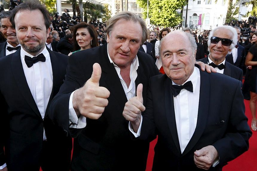 Actor Gerard Depardieu (centre), Fifa President Sepp Blatter (right) and director Frederic Auburtin posing on the red carpet for the screening of the film United Passions at the 67th Cannes Film Festival in Cannes, on May 18, 2014. -- PHOTO: REUTERS