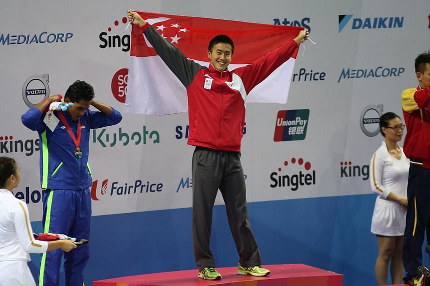 Singapore swimmer Quah Zheng Wen celebrating on the podium after his record-breaking SEA Games gold in the men's 100m backstroke on June 6, 2015. -- ST PHOTO: WANG HUI FEN