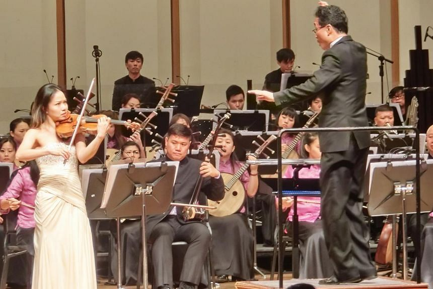 Violinist Kam Ning (left) performing with the Singapore Chinese Orchestra, conducted by Yeh Tsung. -- PHOTO: CHANG TOU LIANG