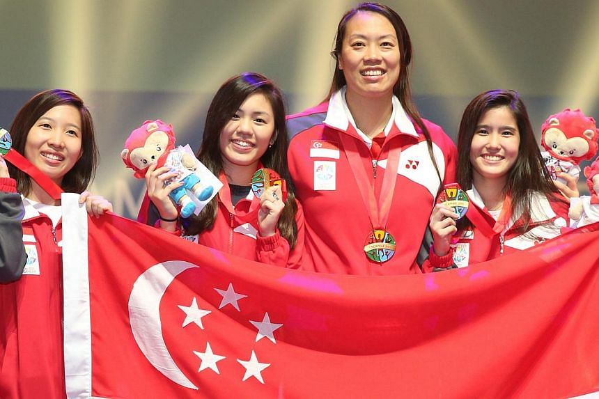 (From left) The women's foil team of Cheryl Wong, Nicole Wong, Wang Wenying, and Liane Wong with their gold medals at the OCBC Arena Hall 2 on June 6, 2015. -- ST PHOTO: KEVIN LIM