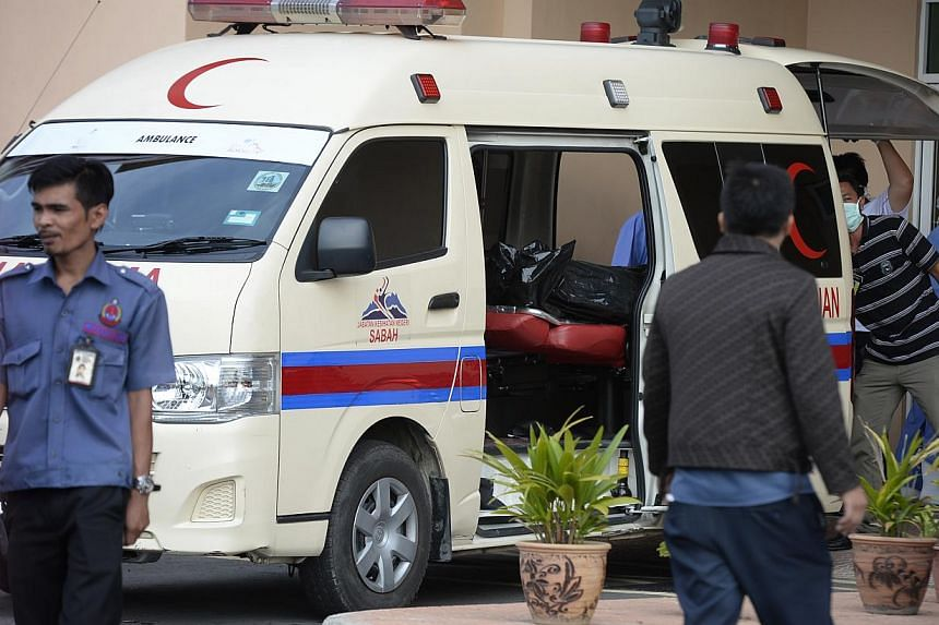 Personnel from the Queen Elizabeth Hospital in Kota Kinabalu unloading a body bag from an ambulance. -- ST PHOTO: MARK CHEONG