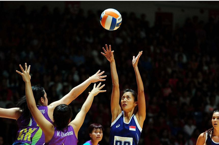 Singapore's Charmaine Soh shoots against Thailand in their netball semi-final on June 6, 2015. Singapore won 59-29 to set up a final clash with Malaysia. -- PHOTO: AFP
