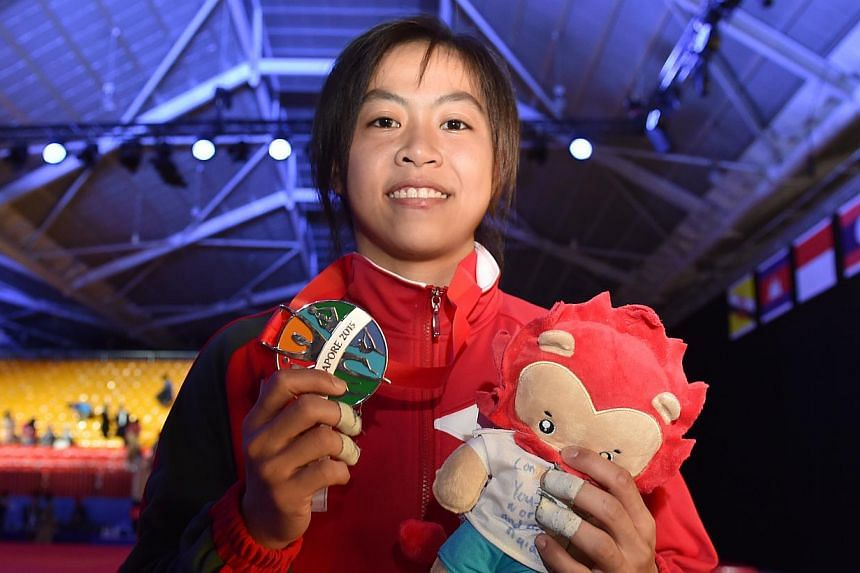 Judoka Ang Xuan Yi holding up the silver medal that she won in the women's 52-57kg event on June 6, 2015. -- ST PHOTO: CAROLINE CHIA