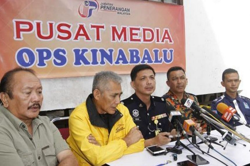 Ranau district police chief Dep Supt Farhan Lee Abdullah (centre) at the media centre in Kinabalu Park. -- PHOTO: THE STAR/ ASIA NEWS NETWORK