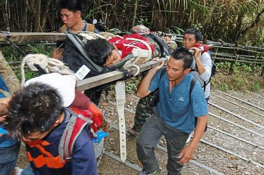 Rescuers carrying an injured climber arriving at the Timpohon Gate at Kinabalu Park. -- PHOTO: THE STAR/ASIA NEWS NETWORK