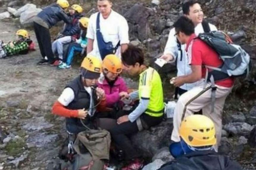 Climbers who were on the lower part of Mount Kinabalu taking a rest as they make their way to the safety. -- PHOTO: THE STAR/ASIA NEWS NETWORK