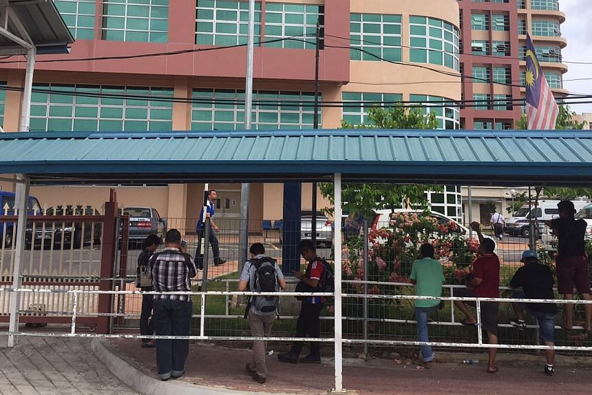 Members of the Malaysian media staking out outside the mortuary at Queen Elizabeth Hospital in Kota Kinabalu where according to Malaysian media, a body of a Singaporean girl arrived earlier today.. -- ST PHOTO: MARK CHEONG