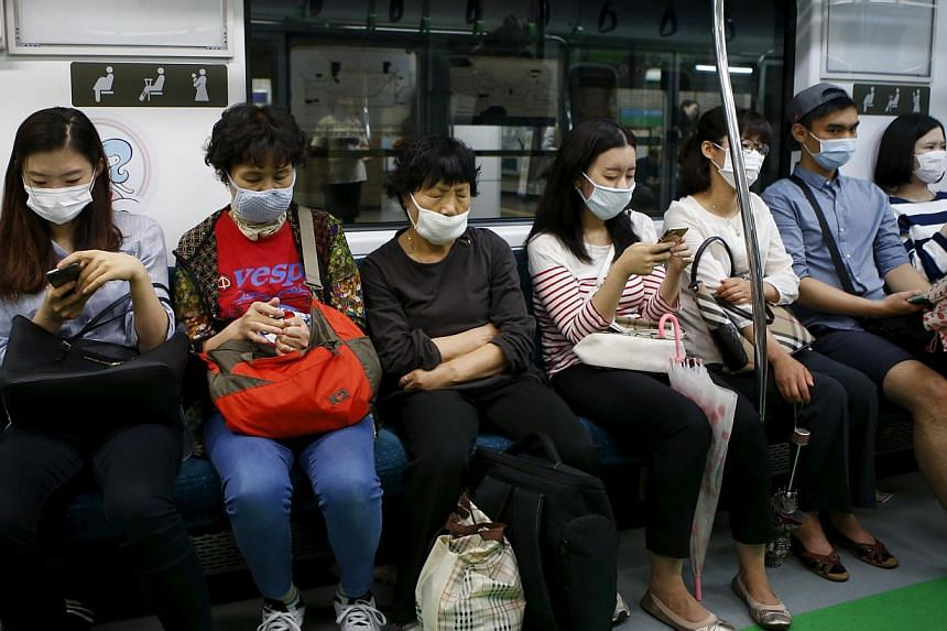 Passengers wearing masks to prevent contracting Middle East Respiratory Syndrome (MERS) sit inside a train in Seoul, South Korea, on June 5, 2015. -- PHOTO: REUTERS