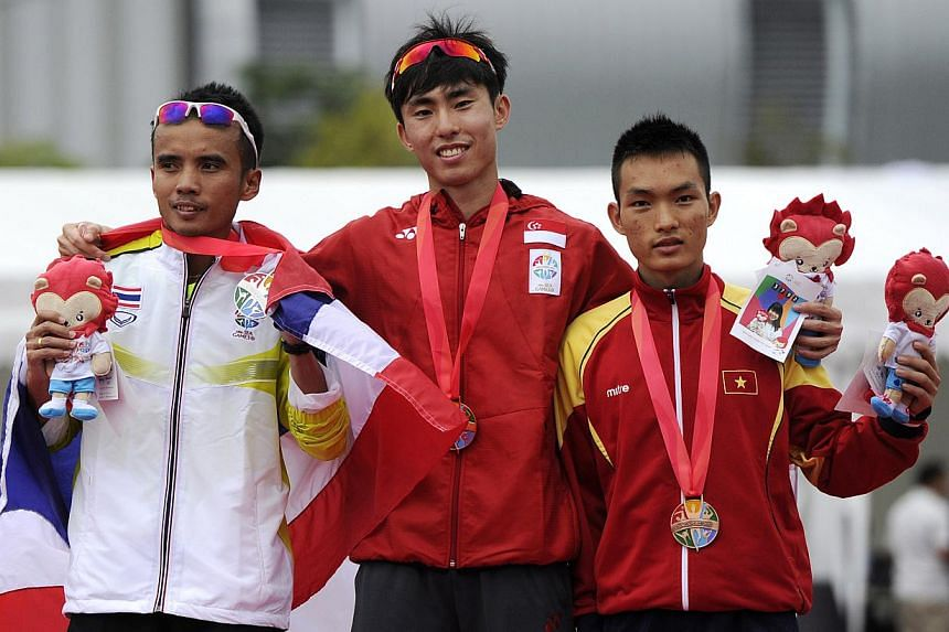 (From left) Thailand's BoonthungSrisung, Singapore's Soh Rui Yong and Vietnam's Nguyen Thanh Hoangon the podium after the SEA Games men's marathon event. Soh won the gold, beating Srisung (silver) over the last 200m of the race. -- PHOTO: