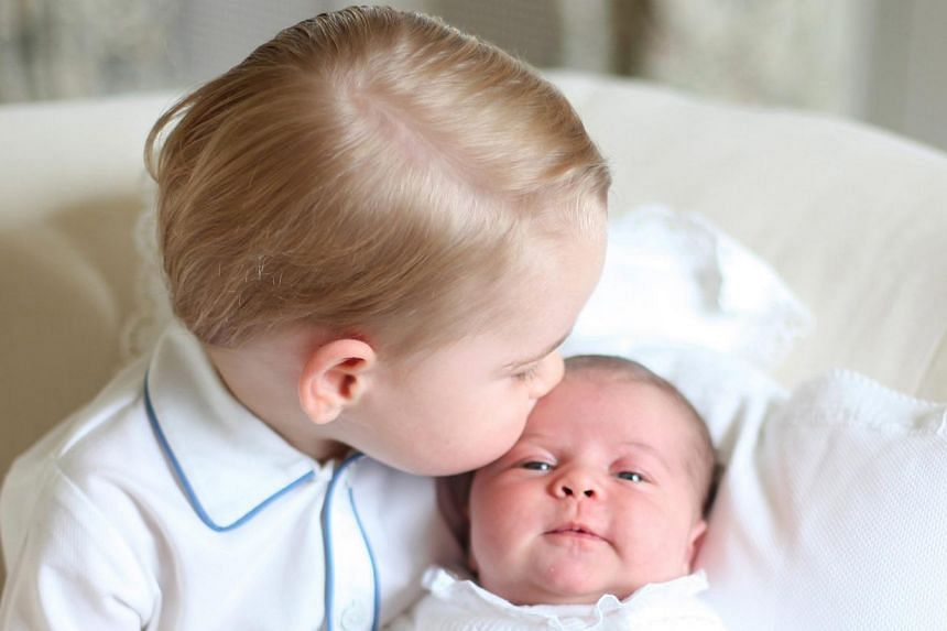 Britain's Prince George kisses the forehead of his baby sister, Princess Charlotte, in this handout photo released by Britain's Prince William, Duke of Cambridge, and his wife Catherine, The Duchess of Cambridge, on June 6, 2015, at Anmer Hall in Nor
