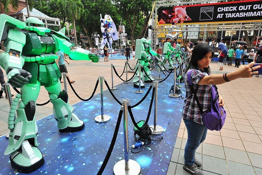 Michelle Pang, 38, Production Worker, taking a selfie with 1.7m Zaku models at the outdoor space of Ngee Ann City Civic Plaza on June 6, 2015. -- PHOTO: LIM YAOHUI FOR THE STRAITS TIMES