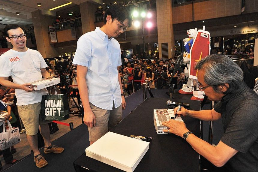 Mechanic designer Mr Kunio Okawara, signing autographs for fans, at Takashimaya Square on June 6, 2015. -- PHOTO: LIM YAOHUI FOR THE STRAITS TIMES