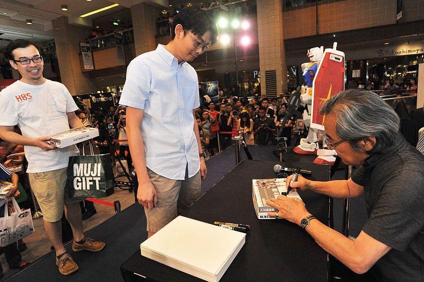 Mechanic designer Mr Kunio Okawara, signing autographs for fans, at Takashimaya Square on June 6, 2015. -- PHOTO: LIM YAOHUI FOR THE STRAITS TIMES