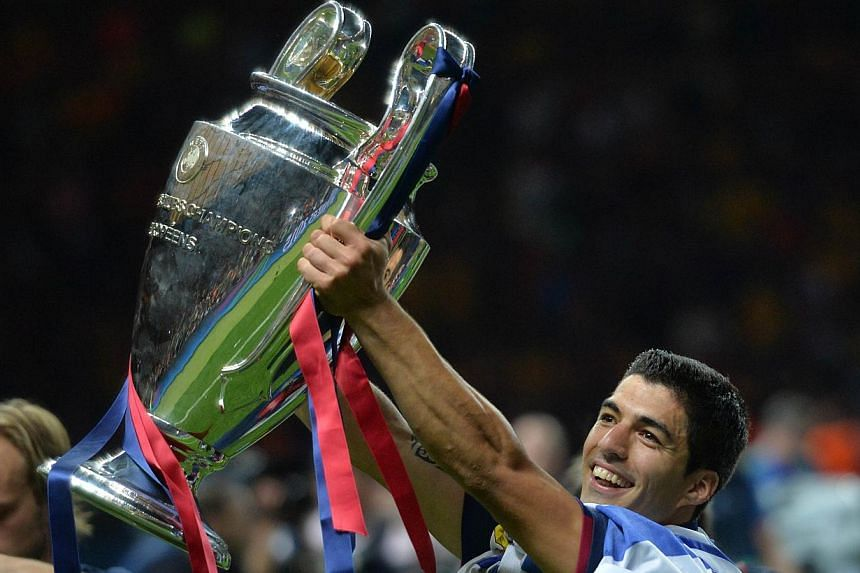 Barcelona's Uruguayan forward Luis Suarez celebrates with the trophy after the UEFA Champions League Final football match between Juventus and FC Barcelona at the Olympic Stadium in Berlin on June 6, 2015.