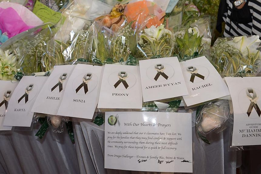 Bouquets of flowers in memory of the victims laid out on a table at Tanjong Katong Primary School. -- ST PHOTO: DESMOND WEE