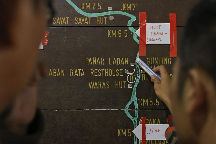 Malaysian rescue officials mark their current locations on the information board located on the way to Mount Kinabalu during a rescue mission for more than 130 climbers who were stranded on one of Southeast Asia's highest mountains after an earthquak
