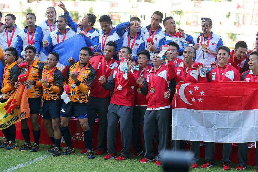 Singapore's SEA Games men's rugby 7s team (above) had to settle for a bronze medal, while the women took silver. -- PHOTO: THE NEW PAPER