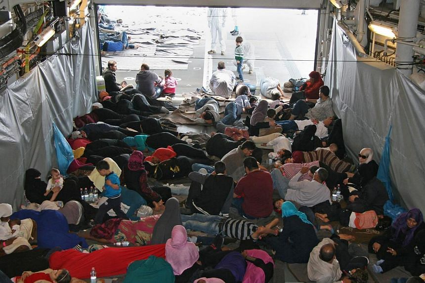A photo provided by the German Armed Forces (Bundeswehr) shows rescued migrants sitting in the shadow on a deck of the German Navy frigate Hessen at an unspecified location in the Mediterranean Sea on June 6, 2015. -- PHOTO: EPA