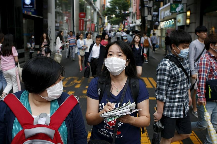 Chinese tourist wearing masks to prevent contracting Middle East Respiratory Syndrome (MERS) walk at Myeongdong shopping district in central Seoul, South Korea, on June 5, 2015. -- PHOTO: REUTERS