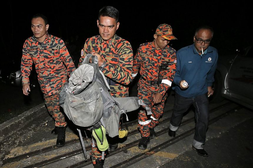 ABOVE: Emotions running high at Changi Airport yesterday as parents reunited with their children who had gone to Mount Kinabalu on a school trip. LEFT: Members of a Malaysian Fire and Rescue Department team with a bag containing part of a body retrie