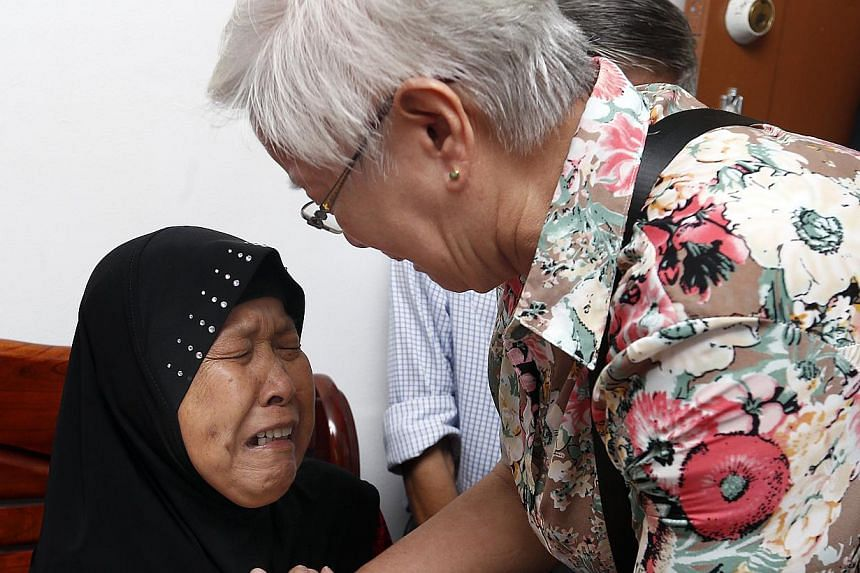 (Above) Madam Zawiah Ahid (with headscarf) meeting (from left) sixth sister Teo Kiat Chit, 74, third sister Teo Suak Huay, 85, and fifth sister Teo Suat Way for the first time since her adoption soon after birth. (Below) She could not stop her tears