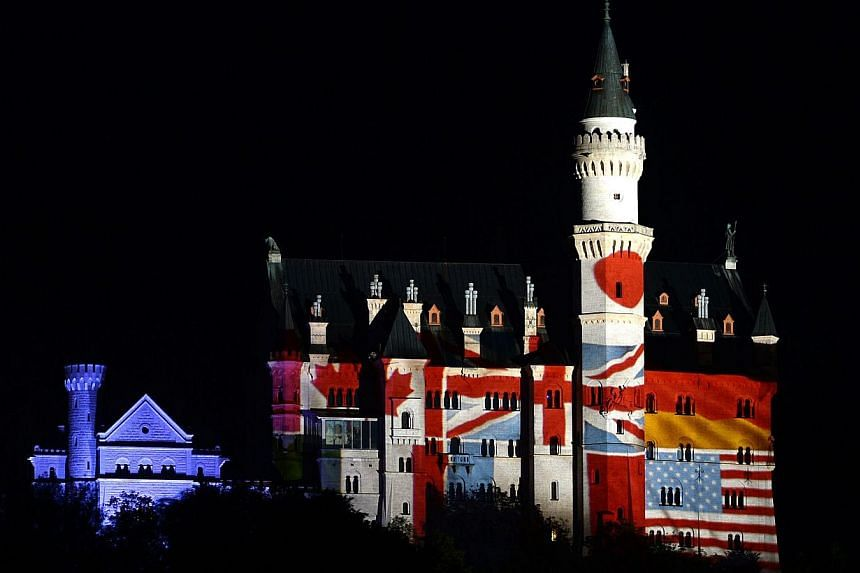 The castle Neuschwanstein near the small Bavarian village Fuessen, southern Germany, is illuminated with the national flags of the G7 countries in the evening on June 5, 2015. -- PHOTO: AFP