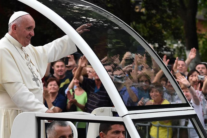 Pope Francis waves to the crowd from the popemobile on his way to an inter-religious meeting with the archbishop of Sarajevo, Cardinal Vinko Puljic, as part of a one day visit in Bosnia, on June 6, 2015 in Sarajevo. -- PHOTO: AFP
